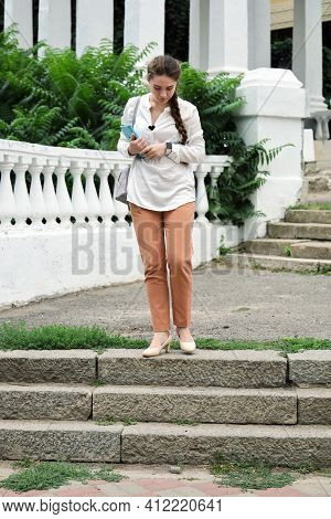 Young Woman Stands On Top Of Concrete Staircase And Looks Down To Go Down Steps And Do Not Fall In H
