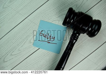 Guilt Write On Sticky Notes With Gavel Isolated On Wooden Table.