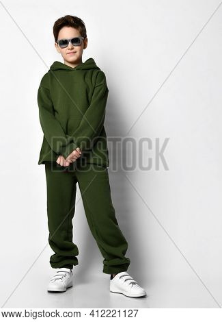 Full Portrait Of A Frisky Smiling Guy In Modern Green Tones, With A Hood, A Sweatshirt Standing Mode