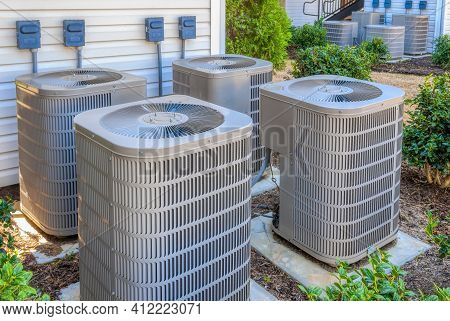 Horizontal Shot Of Four Air Conditioning Units Outside Of An Upscale Apartment Complex.