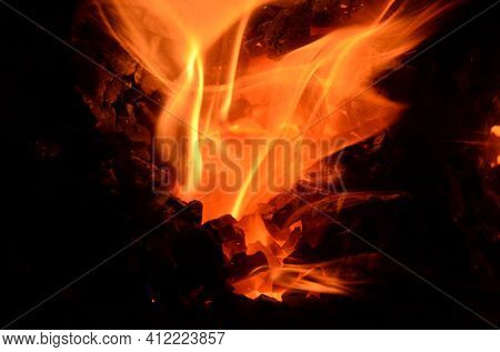 A Flame Of Burning Coal Bursts Out Of The Hole Between The Masses Of Coal.