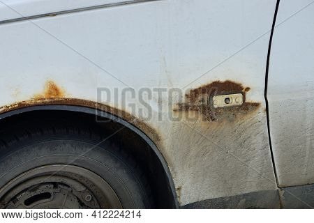 Part Of An Old White Passenger Car From A Metal Fender In Gray Mud And Brown Rust Over A Black Wheel