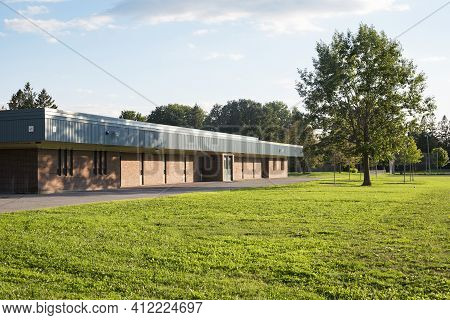 School Building And Schoolyard With Green Field And A Tree