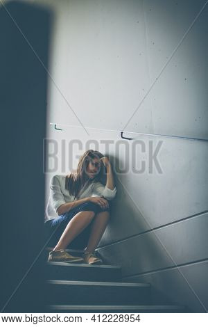 Depressed young woman sitting in a staircase, jobloss due to coronavirus pandemic, Covid-19 outbreak. Unemployment, economic crisis, financial distress concept
