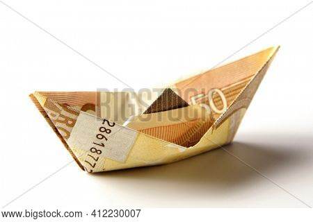 Paper boat folded from European Euro currency bill on white background