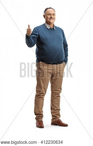 Full length portrait of a cheerful mature man gesturing a thumb up sign isolated on white background