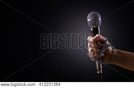 World Press Freedom Day Concept. Hand Holding A Microphone With Chain On Dark Background, Symbol Of