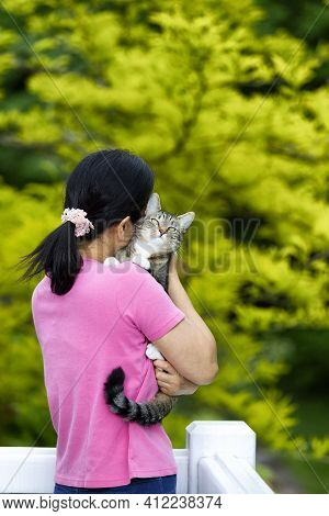 Woman Hugging Smug Looking Family Pet Cat While On Outdoor Home Deck With Back To Camera