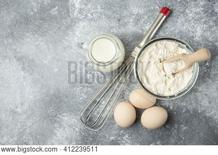 Flour, Eggs, Milk And Whisker On Marble Background
