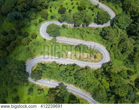 Aerial View Of Curve Road Cut Throug The Green Forest In The Highland Mountains In Chiang Rai Provin