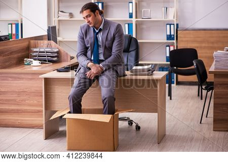 Young male employee being dismissed from his work