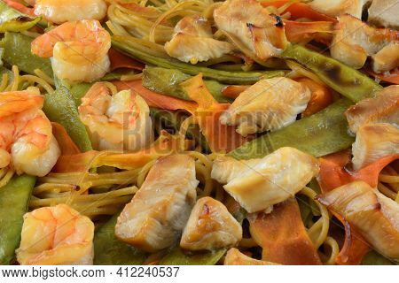 Closeup Of Shrimp And Chicken Casserole With Carrots, Snow Peas And Pasta