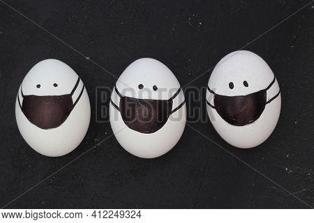 Easter Egg On Medical Masks On A Black Background. Easter Background.creative Easter Eggs With Coron