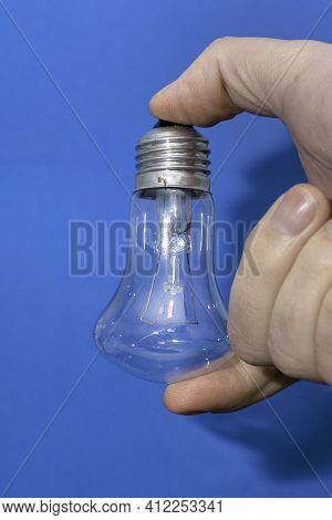 Incandescent Lamp In The Hand Of A Person On A Blue Background