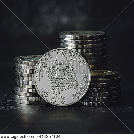 Commemorative Coin Dedicated To The Symbol Of 2021 On The Background Of Stacks Of Silver Coins On A