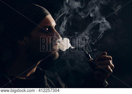 Man Smoking A Pipe On Dark Background. Back Lit Profile Portrait.