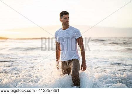 Attractive Muscular Young Athletic Man Standing In The Ocean. Fashion Photo.
