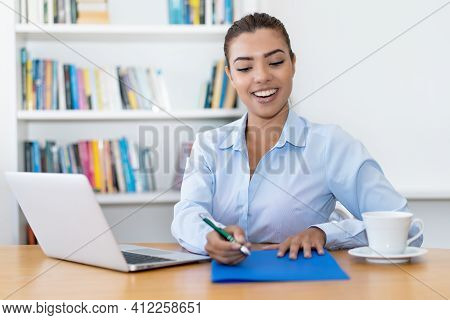Laughing Latin American Business Trainee With Paperwork At Desk At Office