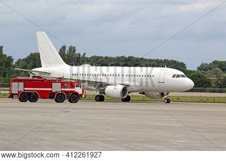 Passenger White Plane And A Fire Truck At The Airport. Place For Text. Runway. Travel. Taxiing. Take