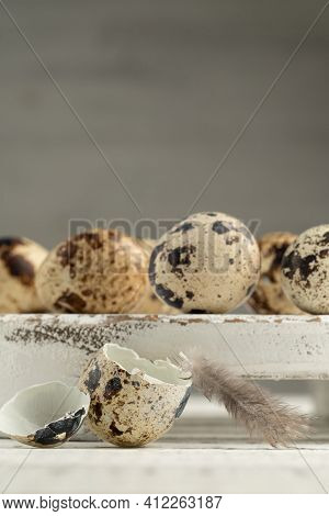 The Shell Of A Broken Quail Egg And Feather. At The Back Are Whole Quail Eggs On A White Wooden Boar