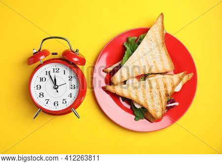 Tasty Sandwiches And Alarm Clock On Yellow Background, Flat Lay. Nutrition Regime