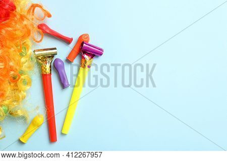Party Blowers, Balloons And Clown Wig On Light Blue Background, Flat Lay. Space For Text