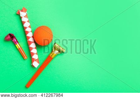 Party Blowers, Clown Nose And Chinese Finger Trap On Green Background, Flat Lay. Space For Text