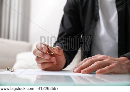 Man With Wedding Ring And Divorce Papers At Table Indoors, Closeup. Space For Text