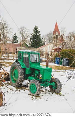 Typical Wooden House In The Countryside With Old Green Tractor Belarus In The Garden In Winter, With