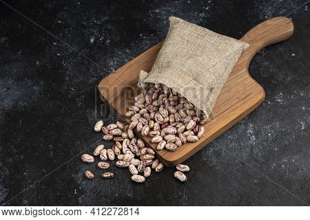 Sackcloth Of Dried Raw Beans Placed On Wooden Board