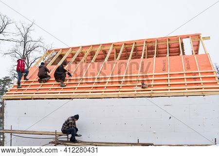 Irpin - Ukraine, March - 13, 2021: Roofing Contractors Installing Roof Boards And Vapor Barriers For