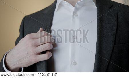 Close-up Of Gentleman Adjusting Suit Jacket. Action. Attractive Man Adjusts Tuxedo Before Celebratio