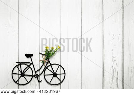 Small wire bicycle with flowers on wooden background