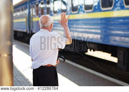 An Old Man Farewell To His Children At The Railway Station. Rear View. He Waves His Hand