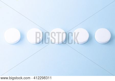 Round White Medical Pills On A Blue Background. Health Concept