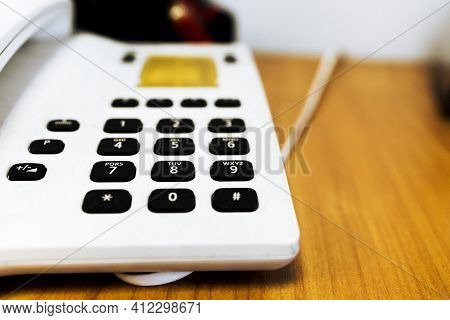 Vintage Push-button White Phone With Black Buttons On The Table, Blur