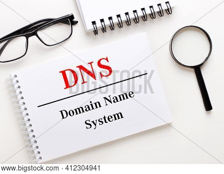 Dns Domain Name System Is Written In A White Notebook On A Light Background Near The Notebook, Black