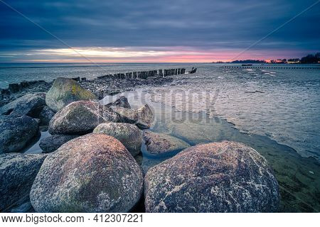 Long Breakwater At Cloudy Sunset. Big Rocky Stones In Dutch Lake At Twilight In The Early Morning