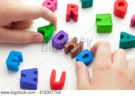 A Young Boy Holding The Abbreviation Adhd That Is Made Out Of Polymer Clay Letters. Adhd Is Attentio