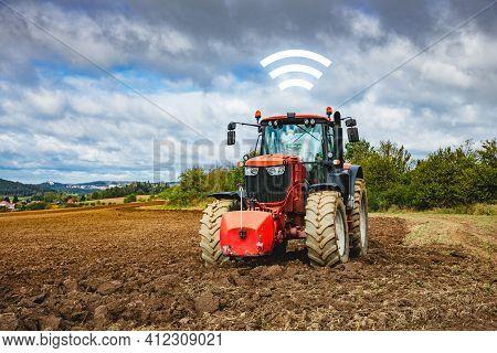 Autonomous Tractor And Intelligent Agriculture Concept. Autonomous Tractor On Plowed Field Communica