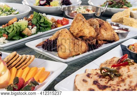 Full Table Of A Variety Of Restaurant Dishes To Choose From With Roasted Chicken Wings In The Center