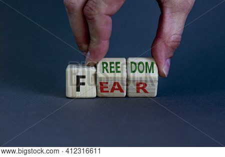 Freedom From Fear Symbol. Businessman Turns Wooden Cubes And Changes The Word 'fear' To 'freedom'. B