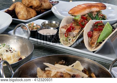 Full Table Of A Variety Of Restaurant Dishes To Choose From With Pan Roasted Fish Tacos In The Cente