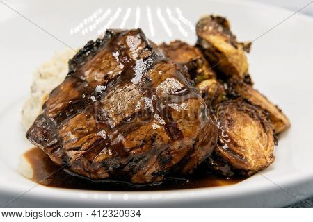 Filet Mignon Steak Glazed In Sauce Served With Roasted Brussel Sprouts Halves On A Plate For Dinner.