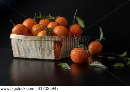 Fresh Tangerine Lies On A Black Table In The Background There Is A Basket With Tangerines.