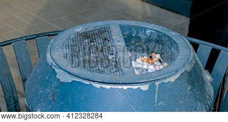 Cigarette Butts In A Round Metal Public Urn. Container For Cigarettes. Anti-smoking Concept.