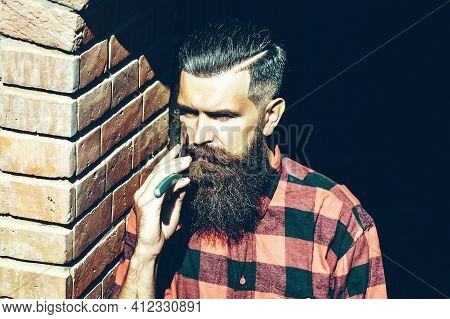 Hipster With Haircut And Thick Beard Holding Old Fashion Razor With Serious Face. Bearded Client Vis
