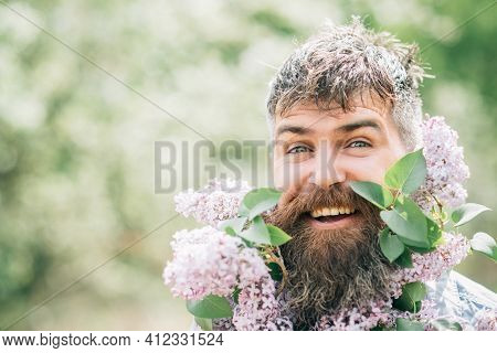 Man With Beard Of Flowers. Happy Bearded Man Smile With Lilac Flowers On Sunny Day. Hipster Enjoy Sc