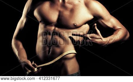 Athlete Waist With A Tape. Sports Nutrition. Closeup Of Young Naked Man With Strong Muscular Beautif