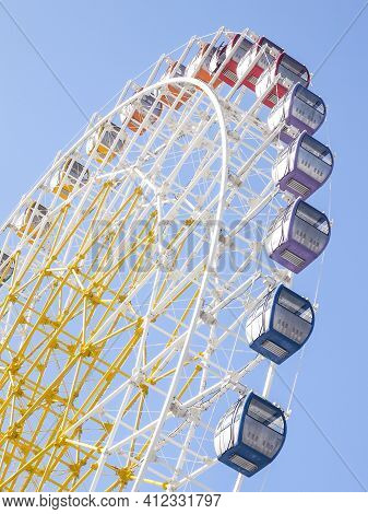 Ferris Wheel In Vivid Colors. Bottom View Of A Colorful Ferris Wheel Against The Sky.